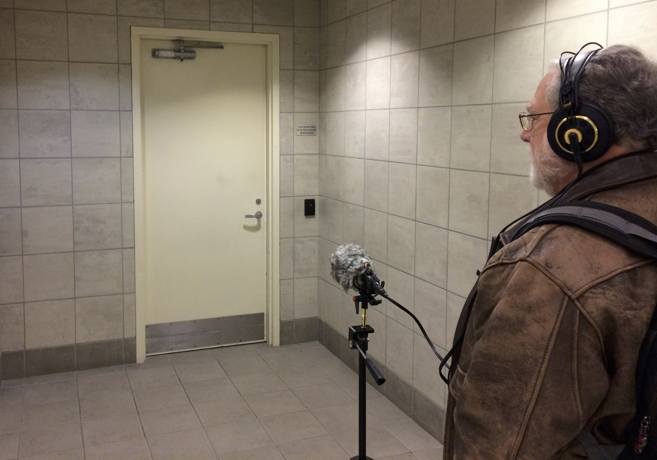White male wearing headphones with recorder listening to sound in a hallway